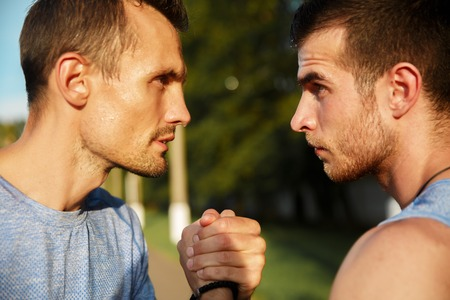 Outdoors portrait of two sporty men handshake on hot summer day