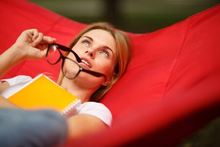 Thoughtful girl with glasses in hands rests in hammock Stock Photo