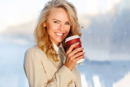 Portrait of elegant happy woman with bright smile holding coffee takeaway standing in front of window in the office Stock Photo