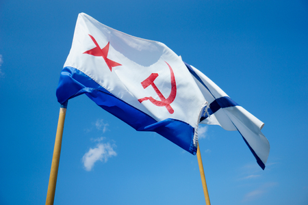 Two flags on background of blue sky. Naval flag of the USSR - red star, hammer and sickle. And Naval flag of Russia. Sevastopol. Crimea Stock Photo