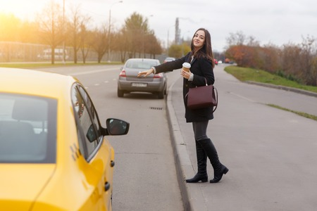 Smiling brunette with long hair stop yellow taxi near road in autumn Stock Photo