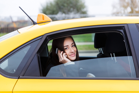 Beautiful brunette with long hair talking on phone in open window of yellow taxi