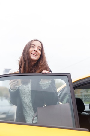 open autocar auto: Smiling young brunette standing at open door of car