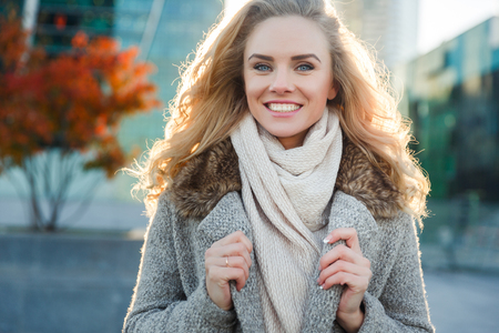 Portrait of young woman in wool coat sitting on background of autumn trees in city