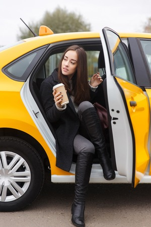 Beautiful brunette with coffee in hand coming out of yellow taxi Banco de Imagens - 66439373
