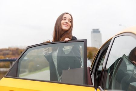 open autocar auto: Young brunette with long hair standing on street at open door of yellow taxi