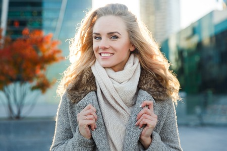 Portrait of happy woman in woolen coat background of autumn trees in city Stock Photo