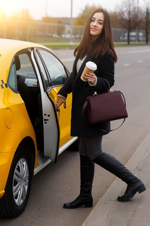 Beautiful brunette in black coat opening door of yellow taxi in afternoon in city Stock Photo