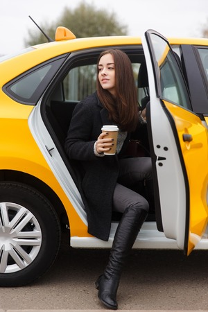 Beautiful girl with long hair sitting in yellow taxi with open door Stock Photo