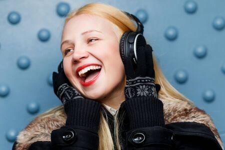 Ginger happy girl in headphones enjoying music at blue wall