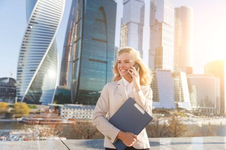confident business woman: Outdoors portrait of confident business woman in suit talking on phone and smiling. Image with lens flare effect