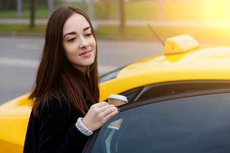 Beautiful brunette in black coat siting in yellow taxi in afternoon in city Stock Photo