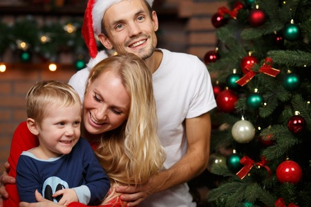 decorate: Family with young son at New Year tree