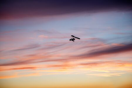 Hang glider flying in clouds of sky at sunset Stock Photo