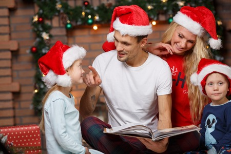 family  room: Loving family in Santa caps with book in Christmas room
