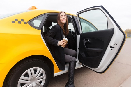 Beautiful young woman with coffee in hand sitting in taxi with the door open