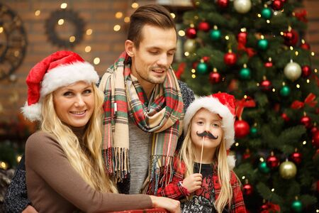Family with daughter with attributes of new year at New Year tree