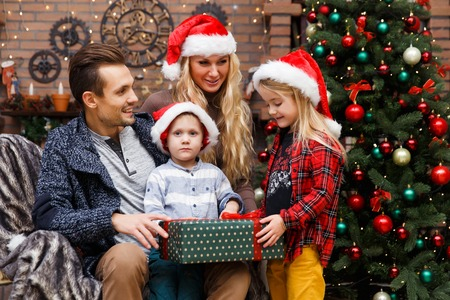 Family with two children opening gifts at New Year tree Stock Photo