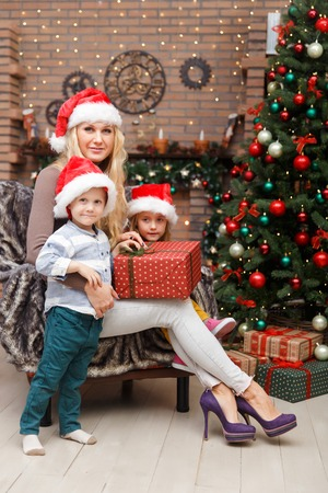 Happy mother with two children in Christmas interior Stock Photo