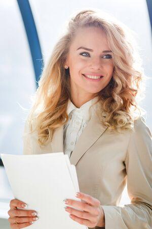 職場で若年労働者の肖像画。紙を折る青い目をした金髪の女性 写真素材