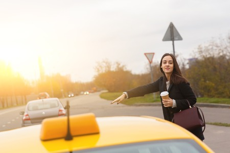 Young brunette with burgundy bag stoping yellow taxi near road Banco de Imagens - 66440868