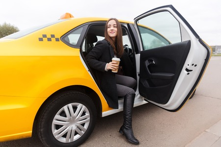 Beautiful young brunette with coffee in hand sitting in taxi with door open