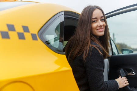back seat: Smiling young brunette caucasian woman posing from the back seat of classic yellow taxi