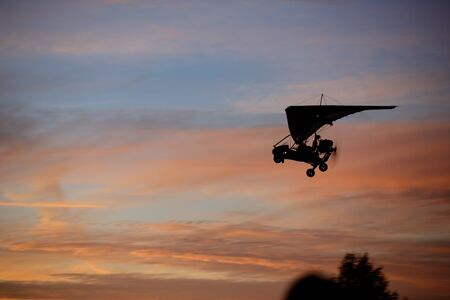 parachute jump: Hang glider flying in sky at sunset Stock Photo