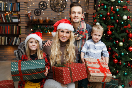 Happy family with two children with Christmas gifts