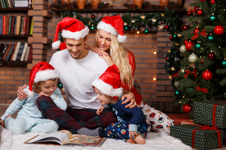 Photo of beautiful family in Christmas interior with Christmas tree Stock Photo