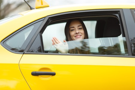 open autocar auto: Beautiful brunette waves hand in yellow taxi window