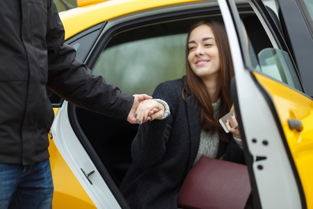 open autocar auto: Cheerful girl sitting in yellow taxi takes hand to young man Stock Photo