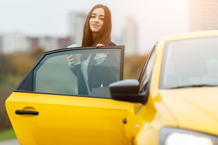 open autocar auto: Beautiful woman with coffee in hand coming out of yellow taxi with door open.