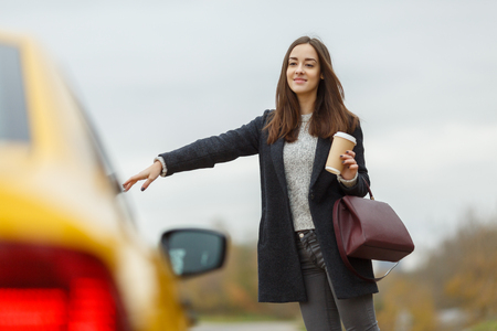 open autocar auto: Beautiful brunette on road stop yellow taxi
