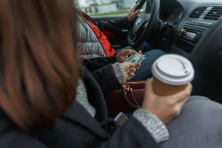 open autocar auto: Young woman with coffee in hand coming out of taxi