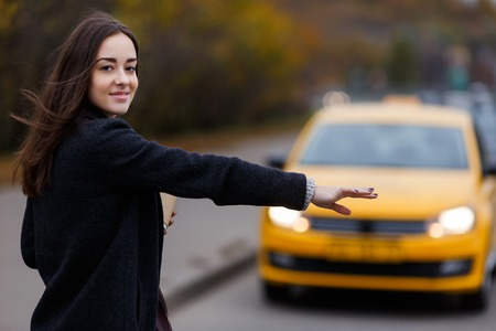 Smiling young woman tries to stop taxi. Model looking at camera