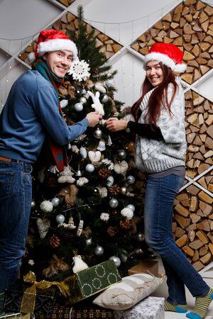 adorning: Smiling pair adorning Christmas pine in Santa hat