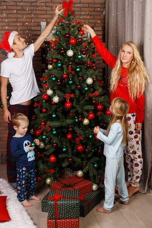 decorate: Happy family decorates Christmas pine in holiday