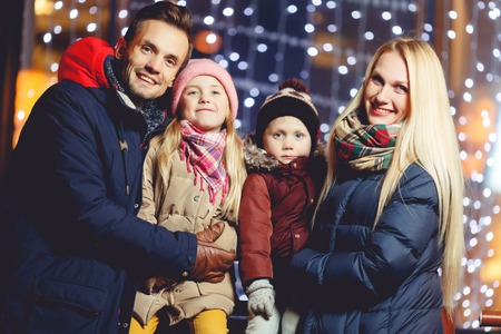 happy family nature: Cheerful family with kids against backdrop of night lights on winter evening