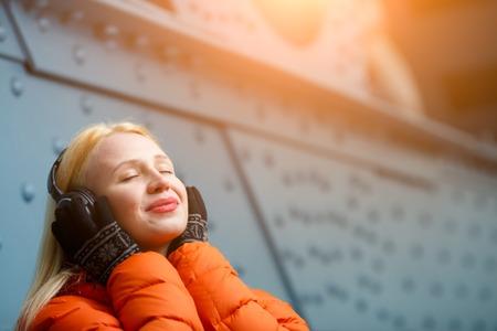 relishing: Girl in orange jacket relishing music on headphones indoors
