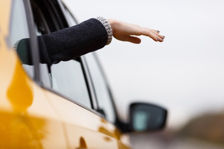 Girl extends hand from open window of yellow taxi