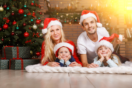 Parents with two children on soft plaid in Christmas tree.