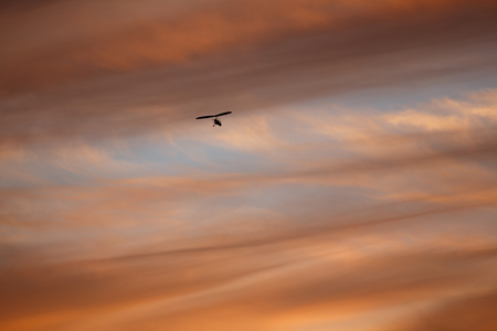 hang-glider flying away in sky at sunset Stock Photo