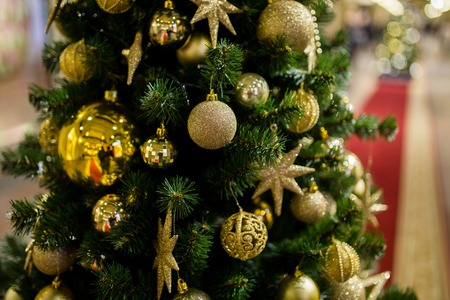 christmastide: Festive pine with golden ornaments on blurred background shopping center