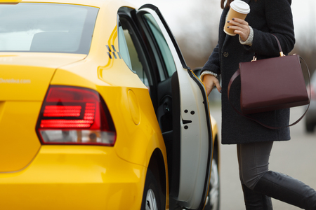 open autocar auto: Girl with brown bag opening door of yellow cab