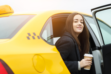 Cheerful brunette with glass of coffee in hands sitting in yellow taxi with door open
