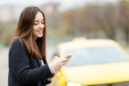 Brunette with cell phone in hand next to yellow taxi Stock Photo