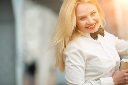 sweetly: Happy young blond woman in white shirt with tie and bright red lips smiling sweetly. Image with lens flare effect