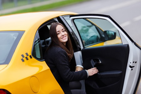 Portrait of young happy brunette woman with coffee in backseat of taxi with the door open. Model looking at camera