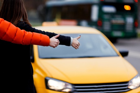 Businesswoman with man stopped taxi on street during day